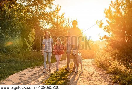 Father with daughters standing holding hands and golden retriever on leash outdoors at sunset