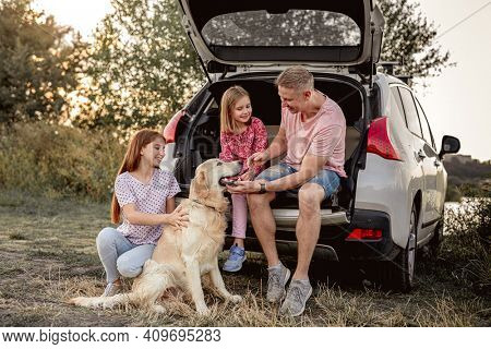 Father with daughters and golden retriever sitting in car trunk on nature