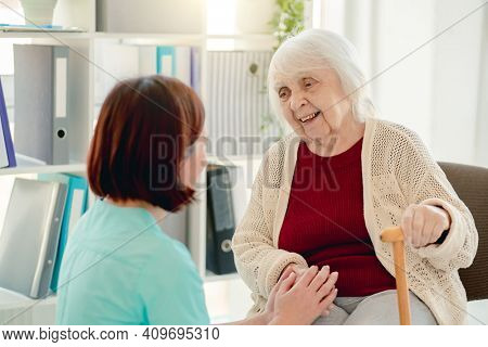Old lady talking to caregiver holding hands in nursing home