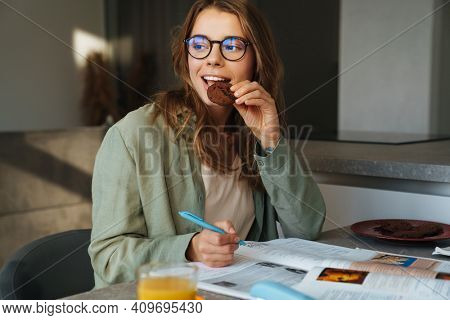 Pleased nice student woman eating cookie while doing homework at home