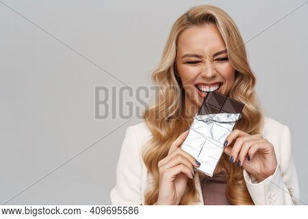 Happy gorgeous woman smiling while eating chocolate isolated over grey background