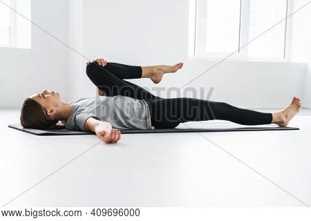 Athletic focused sportswoman doing exercise during yoga practice indoors