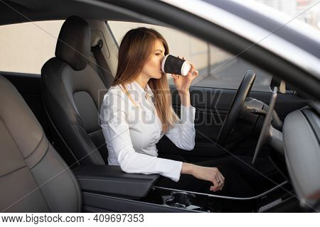 Young Pretty Businesswoman Drinking Take Away Coffee, Sitting Inside Of Autonomous Driverless Electr