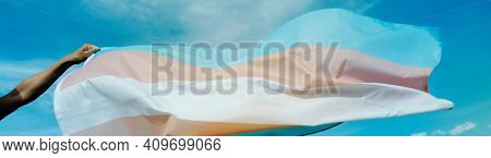 closeup of a person waving a transgender pride flag on the blue sky, in a panoramic format to use as web banner or header
