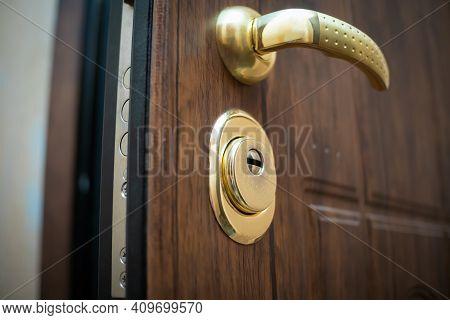 Close-up Of The Golden Handle, The Lock Of The Open Beautiful Brown Front Door