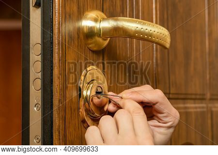 Male Hands Break Open A Brown Front Door With A Lock Pick Close-up