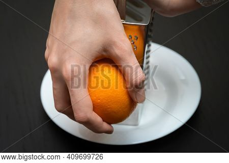 Female Chef Grates Orange Zest With A Grater On A White Plate Close-up