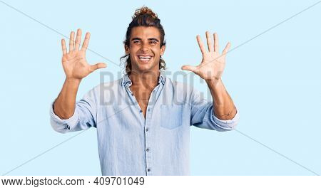 Young hispanic man wearing summer style showing and pointing up with fingers number ten while smiling confident and happy.