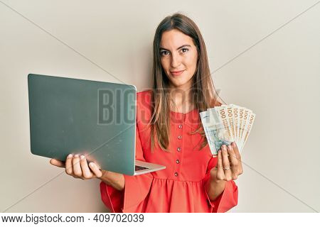 Young beautiful woman holding laptop and denmark krone relaxed with serious expression on face. simple and natural looking at the camera.