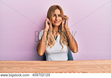 Beautiful blonde young woman wearing casual clothes sitting on the table covering ears with fingers with annoyed expression for the noise of loud music. deaf concept.