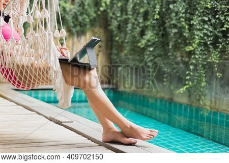Woman In Swimming Suit Sit In Hammock Working On Laptop By Swimming Pool.