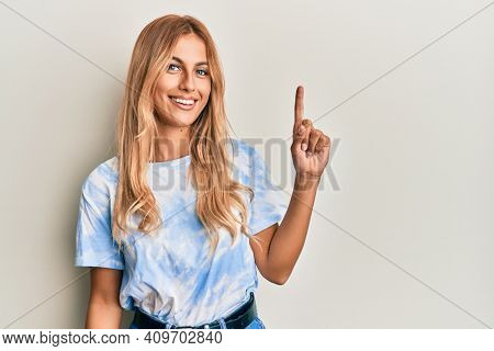 Beautiful blonde young woman wearing tye die tshirt smiling with an idea or question pointing finger up with happy face, number one