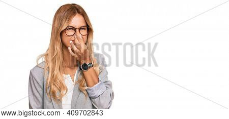 Beautiful blonde young woman wearing business clothes smelling something stinky and disgusting, intolerable smell, holding breath with fingers on nose. bad smell