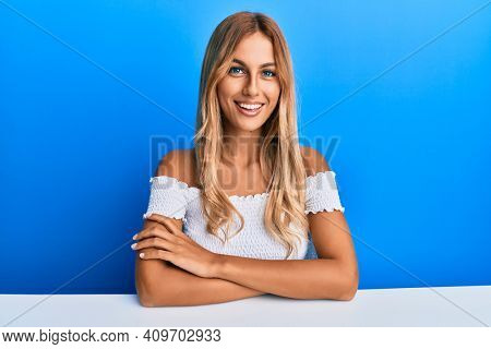 Beautiful blonde young woman wearing casual clothes sitting on the table with a happy and cool smile on face. lucky person.