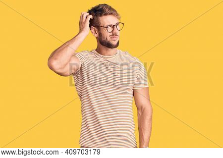 Young caucasian man wearing casual clothes and glasses confuse and wondering about question. uncertain with doubt, thinking with hand on head. pensive concept.