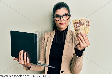 Young hispanic woman wearing business style holding laptop and hungarian forint relaxed with serious expression on face. simple and natural looking at the camera.
