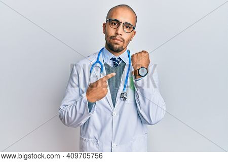Hispanic adult man wearing doctor uniform and stethoscope in hurry pointing to watch time, impatience, looking at the camera with relaxed expression