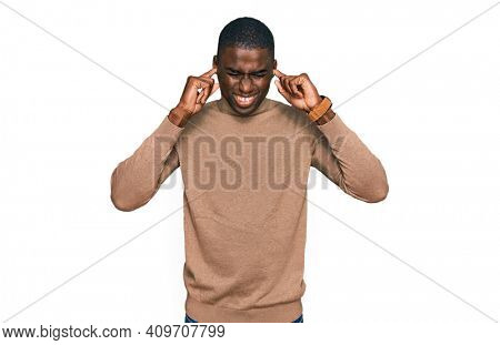 Young african american man wearing casual winter sweater covering ears with fingers with annoyed expression for the noise of loud music. deaf concept.