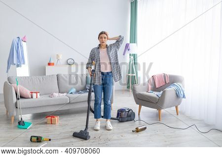 After Party Chaos. Dismayed Millennial Woman Standing In Her Messy Apartment With Vacuum Cleaner, Ho