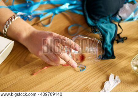 Close Up Of Hand Man Hold A Glass Of Brandy, Sleeping At Table In Messy Room After Bachelor Party, T