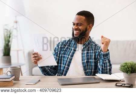 Business Success. Happy African Businessman Reading Papers And Shaking Fists Celebrating Great Deal