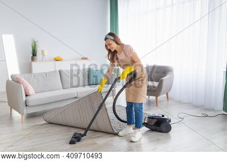 Positive Young Housemaid Tidying Her Apartment, Vacuuming Under Rug, Indoors. Happy Millennial Woman