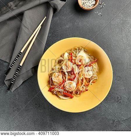 Asian Stir Fried Shrimp and Rice Noodles. Sesame Rice Noodles with Shrimp in yellow plate with wooden chopstick on dark slate table. Asian, authentic food concept.