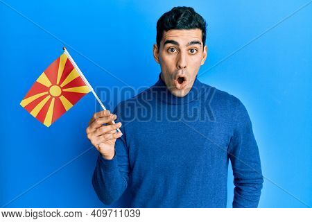 Handsome hispanic man holding macedonian flag scared and amazed with open mouth for surprise, disbelief face