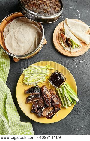 Peking duck chinese food. Yellow plate with vegetables and sauce on dark slate table. Chinese, asian, authentic food concept.