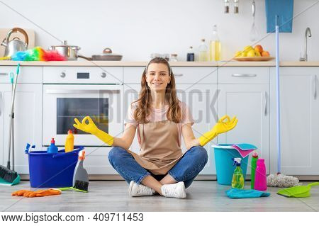 Happy Millennial Housewife Sitting In Lotus Yoga Pose On Kitchen Floor Surrounded By Cleaning Suppli