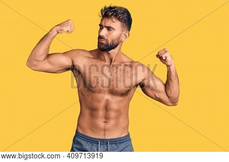 Young hispanic man wearing swimwear shirtless showing arms muscles smiling proud. fitness concept.