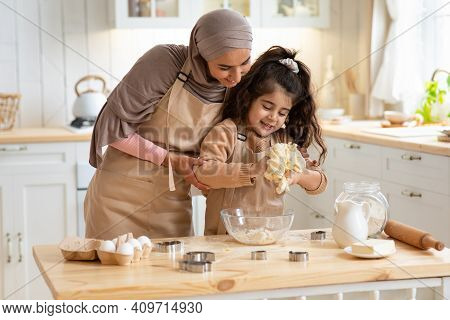 Cute Little Girl And Her Muslim Mom Kneading Dough And Having Fun In Kitchen, Islamic Mother In Hija