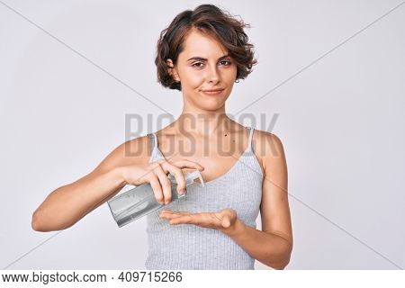 Young hispanic woman using hand sanitizer gel relaxed with serious expression on face. simple and natural looking at the camera.