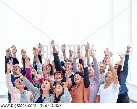 a group of older people raised their hands trying to reach