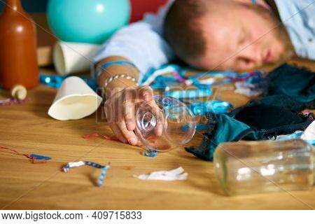 Close Up Of Hand Man Hold A Glass Of Brandy, Sleeping At Table In Messy Room After Bachelor Party