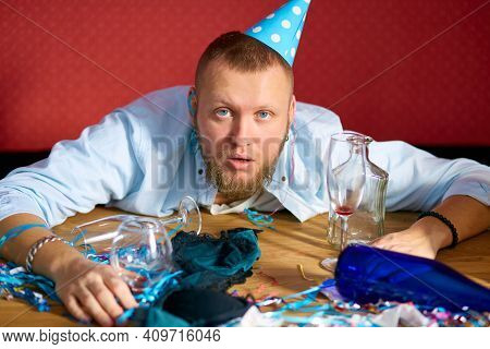 Tired Man At Table With Blue Cap In Messy Room After Birthday Party