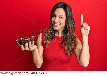 Young latin woman holding bowl with raisins smiling with an idea or question pointing finger with happy face, number one