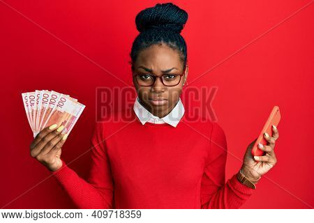 Young african american woman using smartphone holding norwegian krone banknotes skeptic and nervous, frowning upset because of problem. negative person.