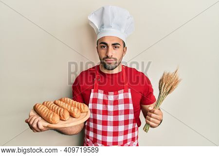Young hispanic man wearing baker uniform holding homemade bread and spike wheat relaxed with serious expression on face. simple and natural looking at the camera.