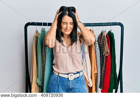 Middle age brunette woman working as professional personal shopper suffering from headache desperate and stressed because pain and migraine. hands on head.