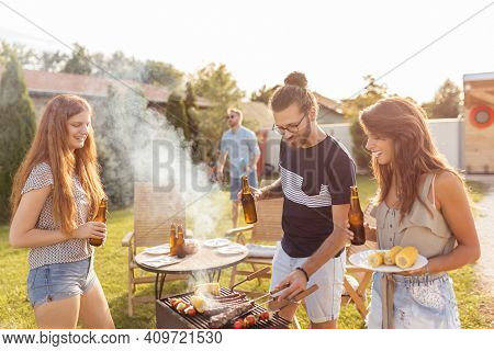 Group Of Cheerful Young Friends Having Fun At Backyard Barbecue Party, Grilling Meat, Drinking Beer,