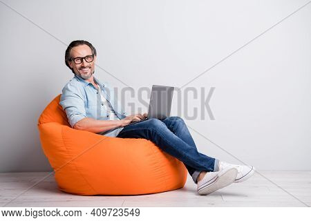 Full Length Photo Of Cheerful Aged Man Happy Smile Sit Chair Programmer Chat Type Laptop Isolated Ov