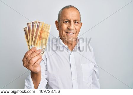 Handsome senior man holding 500 norwegian krone banknotes looking positive and happy standing and smiling with a confident smile showing teeth