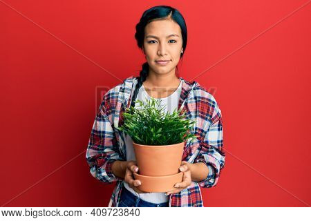 Beautiful hispanic woman wearing gardener shirt holding plant pot relaxed with serious expression on face. simple and natural looking at the camera.