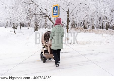Mom With A Stroller Crosses The Road With A Stroller. Pedestrian Crossing In Winter
