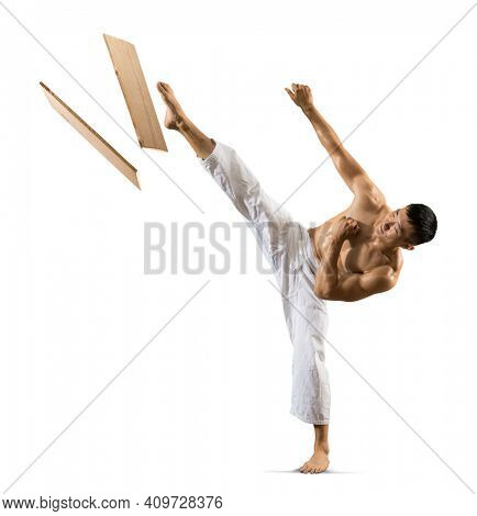 Karate masters breaking with leg wooden board. Isolated on white background
