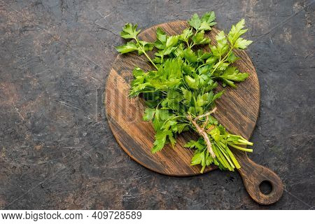 Culinary Backgound, Large Bunch Of Parsley On A Wooden Board Against A Dark Concrete Background. Fre