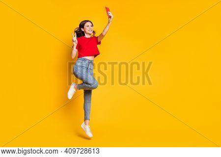Full Body Photo Of Girl Jump Take Selfie Smartphone Make V-sign Wear T-shirt Jeans Isolated Shine Co
