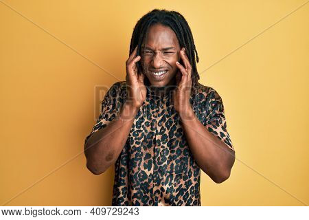 African american man with braids wearing leopard animal print shirt covering ears with fingers with annoyed expression for the noise of loud music. deaf concept.