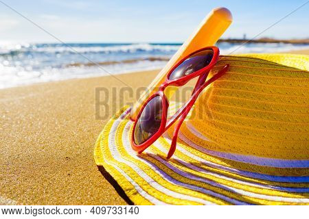 Sun Protection Accessories On Sea Shore. Red Sunglasses, Yellow Straw Hat And Sunscreen Cream Bottle